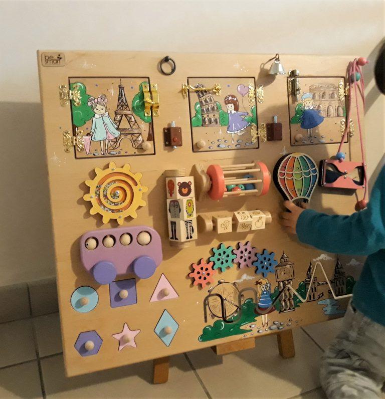 panneau sensoriel avec enfant qui joue dessus